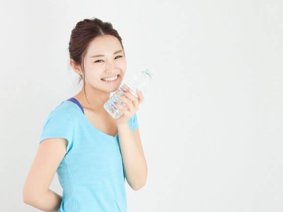 水を頬にあてる女性