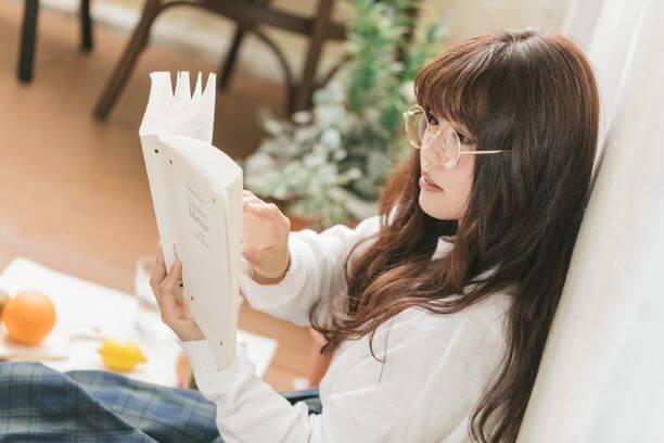 床に座って本を読む女性
