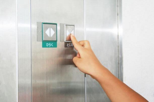 エレベーターで閉じるボタンを押す