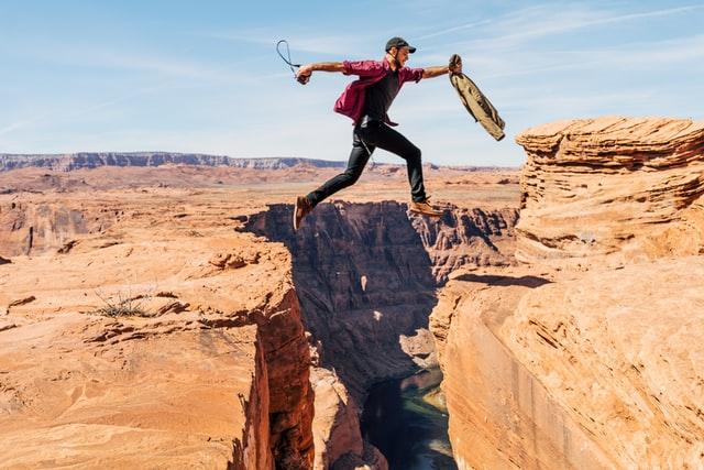 崖を跳び越える男性